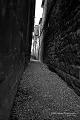 It leads to somewhere... (BLU Jaguar) Tags: light summer blackandwhite texture monochrome wall canon buildings dark mono alley path walk broadway cotswolds alleyway beyond passage narrow pathway gravel 2012