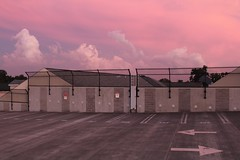 Empty parking lot (elisecavicchi) Tags: parking lot parkinglot evening sundown sunset blush sky clouds pink glow garage treeline tree silhouette fence cement markings maryland gaithersburg olde towne midatlantic humid heavy air bathed empty abandoned heavenly moment natural light