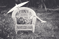 Boy, parasol. and a big cane chair. (goodgirlbetty) Tags: boy parasol rain backyard garden cane chair portrait fine art matte 85mm canon