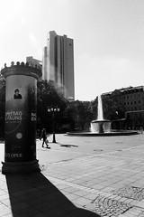 View from Old Opera Frankfurt to German Bank Towers (Notquiteahuman1) Tags: frankfurt frankfurtammain alteoperoperoperaold operafountainstreetstreet sceneagfa apx 100agfanikkornikkor 2885 f3545 aflitfassuleadvertising columnperaruadeutschlandgermanyalemanhanikon f501afternooneveningwide angle wide analog film blackandwhite monocrome