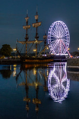 """Russian 1703 frigate """"Shtandart"""" reflecting with the blue lights of the  ferris wheel at Honfleur, Normandy, France (grumpybaldprof) Tags: vieuxbassin oldharbour honfleur normandie normandy france quaistecatherine quaiquarantaine quai quaistetienne stecatherine lalieutenance quarantaine water boats sails ships harbour historic old ancient monument picturesque restaurants bars town port colour bw lights reflection architecture buildings mooring sailing stone collombage halftimbered yachts frigate 1703 shtandart russian tallship sailingship replica ferriswheel bluelights night nightphotography boat ship warshipreflectionswet reflections fregate ruse oldandnew somethingblue nocturne dark"""