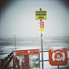 Snow surfing, Leigh-on-Sea (nick richards art) Tags: winter sea england snow signs colour 120 sign thames clouds coast seaside lomo lomography lifebelt 120film diana coastal caution analogue dianaf essex southend windsurf palacetheatre cliffspavilion analoguephotography essexwindsurfclub