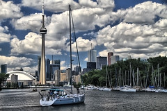 Toronto Skyline (` Toshio ') Tags: city cloud lake toronto ontario canada water sailboat island boat wake waves sailing cityscape cntower cloudy canadian sail ripples lakeontario hdr highdynamicrange hanlanspoint toshio