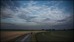 On the Road again (frischauge) Tags: road blue light red sky cloud green field bicycle yellow clouds way landscape evening cyclist sony dramatic s crop curve drama ontheroad acre rx100 wsnature