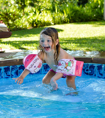 Pool Jump (marccrowther) Tags: flowers blue water pool girl smile swimming 50mm nikon child bokeh hellokitty splash bushes armbands d3200