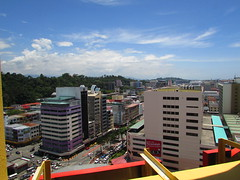 Kota Kinabalu From The Tallest Hotel Downtown (thienzieyung) Tags: city blue windows sky cars skyline clouds buildings high downtown afternoon view traffic angle places hills roofs ridge vehicles busy malaysia shops kotakinabalu intersection cbd hotels geography sabah birdseye wismamerdeka thienzieyung gayacentrehotel