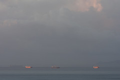 Ships At Sunrise (Jeremy Vickers Photography) Tags: morning sea sun reflection water clouds dark boats spain warm europe ships horizon dramatic floating backdrop gloom costadelsol anchored canonef135mmf2lusm canoneos40d