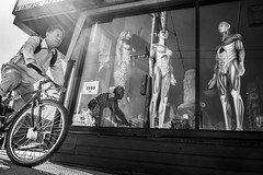 Anatomy for dummies (johnjackson808) Tags: fujifilmxt1 mainst vancouver anatomical bw bicycle blackandwhite curios cyclist flare mannequins monochrome people streetphotography sunburst vintagemermaid window
