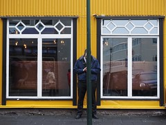 Symmetry in Yellow (Feldore) Tags: man behind pole symmetry symmetrical yellow reykjavik iceland street candid feldore mchugh em1 olympus 1240mm funny texting phone hidden divided