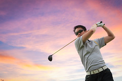 Golfer shooting a golf ball (Patrick Foto ;)) Tags: wood sunset sky playing man game male fashion sport club sunrise ball golf asian thailand glasses twilight asia play power adult cloudy action outdoor background young champion competition swing player thai golfing driver recreation win success challenge golfer active hitting