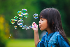 Asian little girl is blowing a soap bubbles (Patrick Foto ;)) Tags: park light summer portrait sun playing game cute green nature girl beautiful face grass childhood smiling female hair season asian fun outdoors happy person one kid spring soap healthy funny pretty child play little joy innocent daughter young meadow happiness bubbles blowing blow human leisure positive lovely playful sunbeam caucasian