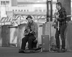 Travelin' Band (Ian Sane) Tags: park street city bridge two white black men musicians tom oregon river portland ian photography downtown waterfront guitar candid board band images piece morrison performers suitcase washer willamette sane mccall travelin