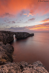 Menorca Sunset. [Explored & FP 10-02-2016] (dasanes77) Tags: canoneos6d canonef1635mmf4lisusm tripod landscape seascape cloudscape waterscape clouds orange blue yellow horizon sea ocean mediterraneansea rocks cliff bridge reflections shadows sunset sun menorca balearicislands spain nature naturallight naturalrockformations calm tranquility