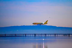 DHL Plane landing at SFO during Sunrise over San Francisco Bay - Millbrae California (mbell1975) Tags: sf california ca blue sea usa water plane sunrise airplane dawn during bay us airport san francisco unitedstates sfo over jet calif landing international flughafen burlingame millbrae dhl
