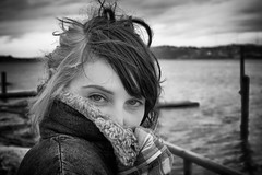 On The Shores of Alki (John Westrock) Tags: seattle portrait blackandwhite woman cold water beautiful female canon eyes bokeh candid coat windy 7d flannel alkibeach washingtonstate janna lookingatthecamera sigma35mmf14