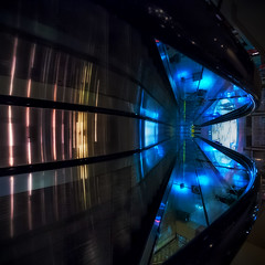 Between Up & Down (Gabriel Tompkins) Tags: blue usa abstract glass lines yellow architecture reflections mall square vanishingpoint washington nikon colorful spokane downtown curves escalator sigma squareformat pacificnorthwest specular railing 1020mm washingtonstate tilt 1020 pnw 1x1 riverparksquare d90 leadingline 2013 inlandnorthwest sigma1020mmf456exdc nikond90 tronam gabrieltompkins