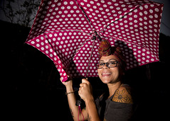 Rainy day sunshine (Blinkofanaye) Tags: woman turban glasses umbrella polka dots surprise tongue teeth smile tattoo headwrap strobe flash street candid baltimore usa 2016