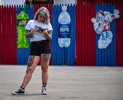 Looking for Pokemon? (tim.perdue) Tags: looking pokemon phone girl woman person figure tattoo ink ohio state fair 2016 summer exposition center columbus street candid colorful multicolored midway fence