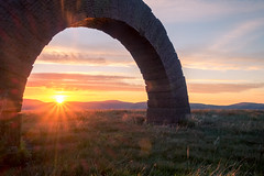 Striding Arch at Benbrack (Strength) Tags: andy goldsworthy andygoldsworthy stridingarches arch sandstone sculpture redsandstone southernuplandway hill hills moor moorland upland scotland dumfriesandgalloway suw sunset hdr sun grass lensflare flare sunstar fuji evening remote wilderness
