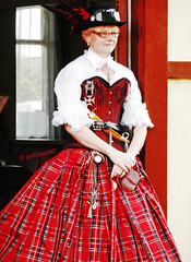 The Lady in Red Tartan (Steve Taylor (Photography) Internet V slow) Tags: red newzealand christchurch woman hat lady notebook glasses belt dress goggles knife canterbury medal blouse doorway nz corset southisland dagger steampunk impressedbeauty flickrdiamond