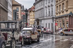 Raining on an antique carpool (beyondhue) Tags: antique car carpool rain cobbled street prague praha czech republic beyondhue travel celetna tourist attraction wet weather summer house building people parking