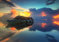 Stranded Boat in Heaven (Fakrul J) Tags: ocean sun reflection beach colors horizontal sunrise island boat ship view sink shoreline rusty serenity malaysia borneo sunk discovery stranded wrecked gettyimages strandedboat