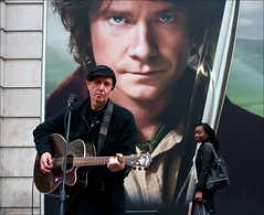 Bilbo and the Busker (Charles Hamilton Photography) Tags: street city portrait people musician girl face poster guitar glasgow streetphotography streetportrait streetperformer busker busking guitarist citycentre bilbobaggins argylestreet thehobbit shopper streetmusician characterstudy peopleinthecity nikond90 alansmart glasgowstreetphotography