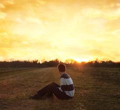 Mercy. (10/52) (alexanderbihn) Tags: boy sunset portrait orange cloud sun field yellow clouds sitting alexander bihn bihni