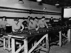 Inspecting gun shells (Tyne & Wear Archives & Museums) Tags: northumberlandroad newcastleupontyne factory vickersarmstrongs women employees industry industrial manufacturing ww2 secondworldwar industrialheritage gunshells military munitions blackandwhitephotograph digitalimage archives interior room wall ceiling lightshade artificiallight brick beam structure construction floor debris table bench timber pipe workers working attentive workshopoftheworld femalemunitionsworkers inspection inspecting 25pdrshells cylinder metal 20november1942 processwork elswickworks scotswoodworks vickersarmstrong rivertyne northeastofengland unitedkingdom products customers williamgeorgearmstrong lordarmstrong armaments elswick scotswood interesting fascinating unusual necklace arm hair row pattern line wartime homefront mark grain ammunition scales weight