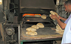 The Baker: His Bread, His Oven and His Cigarette (Colorado Sands) Tags: africa food man male alexandria bread baking baker oven employment cigarette working egypt middleeast menatwork machinery bakery egyptian pan egipto pane smoker cheap egitto inexpensive brot egypte merokok egito bakingbread  flatbread employed eg egipt msr cheapeats freshbread iskandariyah sandraleidholdt roundbread  egyptianbread leidholdt sandyleidholdt