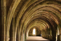 Under the arches lurks a small boy (Wilamoyo) Tags: old light boy england heritage window abbey stone architecture buildings spiral ancient arch child view cross yorkshire small curves religion perspective belief arches structure christian swirls fountains fountainsabbey depth shap