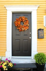 Downtown Door (Karen_Chappell) Tags: door yellow wreath black house rowhouse city urban paint painted wood wooden clapboard stjohns jellybeanrow newfoundland nfld mailbox orange white