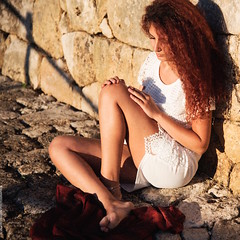 Mediterranean (valerio magini photographer) Tags: woman young hair sitting stones street stonewall wall dress white red colours
