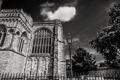 Reaching heavenward (Anthony Plancherel) Tags: architecture category england external hampshire places travel winchester winchestercathedral travelphotography architecturephotography cathedral placeofworship english british greatbritain uk unitedkingdom stone stonework arch classicarchitecture gothicarchitecture window streetlamp fence iron bluesky cloud whiteclouds canon1585mm canon70d canon outdoors blackandwhite whiteandblack bw monochrome trees