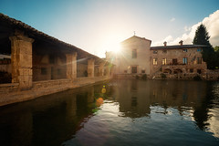 Bagno Vignoni (Philipp Klinger Photography) Tags: city blue light sunset sky italy orange sun hot reflection tree water yellow reflections town back spring nikon warm italia counter antique via val springs tuscany crete siena