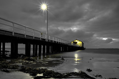 A bleak dawn (Howard Ferrier) Tags: oceania victoria sand rail pier dawn fence overcast marinestructures lamppost clouds lights seaweed inlet beach bay queenscliff portphillipbay shed monochrome reflection jetty storagebuildings australia bellarinepeninsula vegetation au plants time materials photography architecture