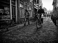 Cyclist 2 (The City) (Daan L) Tags: life street city people urban white black holland monochrome digital mono cyclists leiden noir candid 4 nederland strangers culture documentary social bicycles metropolis rushhour gr nl february schwartz zwart wit weiss iv blanc ricoh fietsen stad fiets straat absorption 2013 dutch thenetherlands richohgrdigitaliv daanl