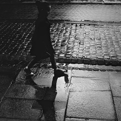 It's the glare from the reflection (martinfowlie) Tags: street blackandwhite wet girl rain contrast shoes shadows paving cobbles howtodestroyangels adrowning