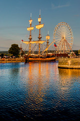"Russian 1703 frigate ""Shtandart"" berthed in golden sunset light near the ferris wheel at Honfleur, Normandy, France (grumpybaldprof) Tags: vieuxbassin oldharbour honfleur normandie normandy france quaistecatherine quaiquarantaine quai quaistetienne stecatherine lalieutenance quarantaine water boats sails ships harbour historic old ancient monument picturesque restaurants bars town port colour lights reflection architecture buildings mooring sailing stone collombage halftimbered yachts shtandart frigate russion 1703 replica tallship warship sailingship sunset golden light yellow blue ferriswheel berth gold gilded"