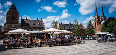 2016 - Baltic Cruise - Roskilde - Central Square (Ted's photos - For Me & You) Tags: 2016 balticcruise tedmcgrath tedsphotos roskilde roskildedenmark denmark plaza roskildecathedral twintowers umbrellas streetscene people peopleandpaths cropped vignetting citysquare