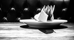 two forks, one knife and a saucer [Explored] (Real Cowboys Drive Cadillacs) Tags: wood blackandwhite white black leather silver booth table restaurant blackwhite fuji silverware bokeh napkin knife fork fujifilm foodcourt italianfood woodgrain saucer woodtable carinos tufting carinositalian fujifilmfinepixx100