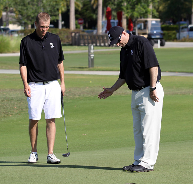 Head Coach Harry Jennings (right) helps freshman Andreas Lunding read a putt at the the Buccaneer Invitational hosted by Barry University. Copyright 2013; Wilmington University. All rights reserved.