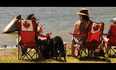 Picnic by the Water (Poocher7) Tags: people outdoor family colemancooler water lake picnic dogs sunglasses hats eating relaxing dreadlocks redchairs canadianflag ontario canada portrait sitting