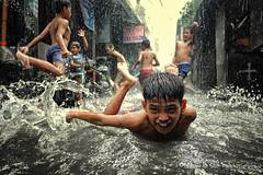 Fun in Monsoon rain and flood (Mio Cade) Tags: rain thunderstorm shower flood kid children boy play manila philippines documentary travel tondo asia fun