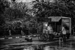 One Last Customer (b&w) (AJ Photographic Art) Tags: asia canon delhi highresolution india travel bw blackwhite cart customer man monochromatic notshotwithmyphone raining selling street streetphotography travelphotography umbrella vendor wet worldtraveler