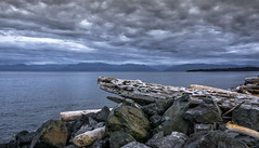 Unsettled.... (Paul Rioux) Tags: britishcolumbia bc vancouverisland colwood westshore westcoast esquimaltlagoon beach driftwood logs clouds outdoor seascape seashore seaside waterfront nature scenic calm water horizon prioux sony a6000 juandefucastrait salishsea