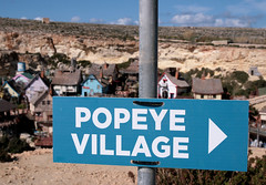 That way to Popeye village (roomman) Tags: blue colour film nature sign set movie walking landscape bay day colours village hiking walk malta hike anchor outlook movieset ta popeye excursion filmset anchors melia mellieha anchorbay 2013 melieha melliea pennellu tapennellu ilmelliea