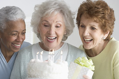 Women Celebrating Birthday --- Image by  Royalty-Free/Corbis (elizabetheastcobber) Tags: birthday friends portrait people food cake dessert women candle friendship joy happiness celebration few birthdaycake gift sweets africanamericans americans blacks whites longevity females customsandcelebrations excitement adults headandshoulders senioradult headandshouldersportrait seniorwoman 60sadult activeseniors