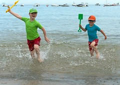 Grandsons at Sea (john atte kiln) Tags: action actionshot boys wet shorts tshirts teeshirts beach water drops waterdrops splashing splashes fun spades toys toyspades hats horizon boats pleasureboats