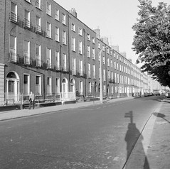 Row of houses, Lower Baggot Street, Dublin (with shadows) (National Library of Ireland on The Commons) Tags: elinorwiltshire rolleiflexcamera rolleiflex wiltshirephotographiccollection nationallibraryofireland elinorobrienwiltshire reginaldwiltshire georgianterrace sunshine pedestrian shadows baggotstreet pembrokestreet dublin photographer evening busstop georgiandublin doorsofdublin explore